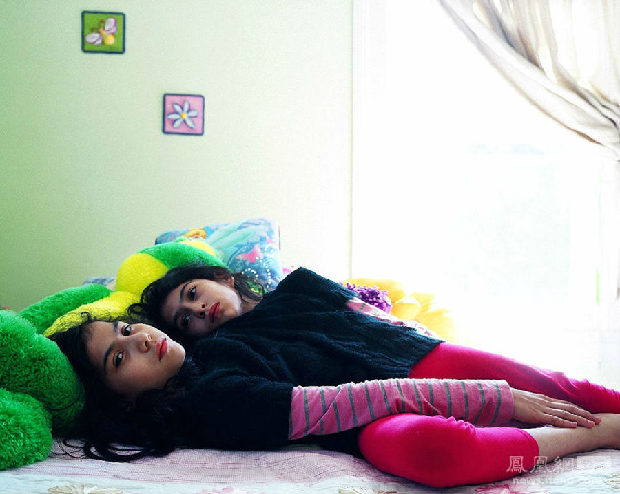 Clark第一次见到这对双胞胎是在她们位于康涅狄格州新米尔福德的家中。两个小女孩儿以令人吃惊的速度灵巧地翻了一个筋斗。Lupita和Carmen还为Clark弹奏了钢琴,Lupita用左手,Carmen用右手。图为2011年,两人躺在床上。