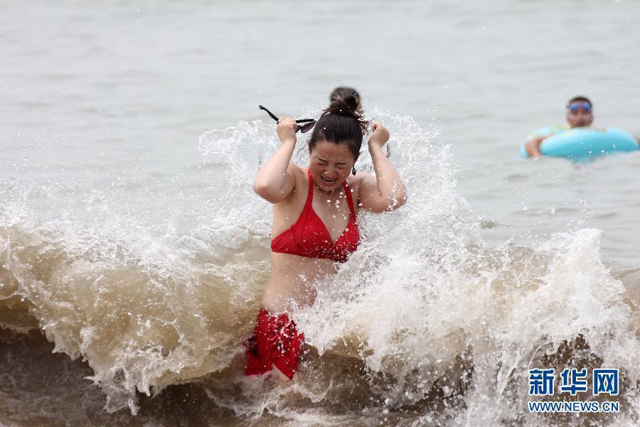 人们在青岛第一海水浴场戏水消暑.